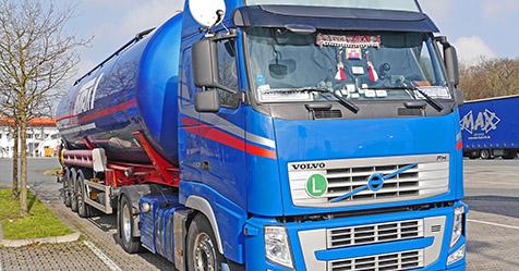 blue lorry towing large tank trailer
